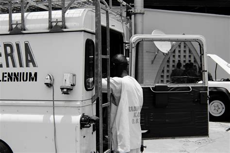 Grayscale Photography of Man Standing Behind Utility Truck